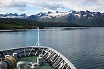 Bow of Hurtigruten ferry ship near Ornes, Nordland, Norway snow capped rugged mountains