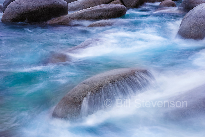 A long exposure of water flowing over a rock on the east shore of Lake Tahoe in Nevada. A long exposure was used to blur the motion of the water.