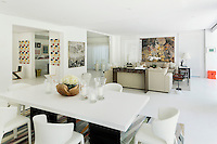 The spacious living/dining area has a light, airy feel with its white walls and flooring.