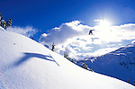 a snowboarder flies into the sun in the British Columbia backcountry near Whistler, BC, Canada.