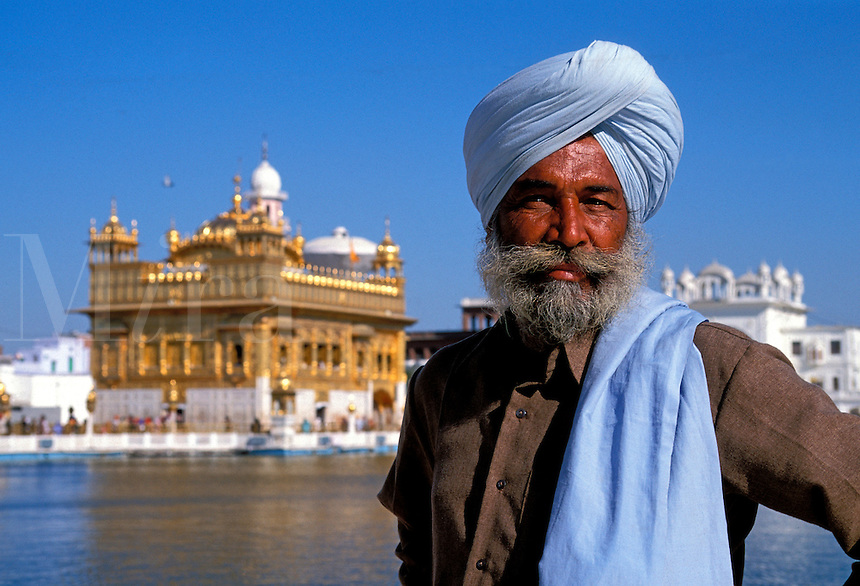 A Sikh wearing the traditional turban stands in front of the shining Golden Temple in the Pool of Nectar in Amritsar in Punjab in northern India. The temple is the holiest shrine of the Sikh religion.
