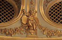 "Detail of Putti, gilded statue in between of the grated boxes (loges grillées) located at the Gods or Paradise (paradis or poulailler in French), upper balcony, Theatre Imperial Napoleon III de Fontainebleau (Fontainebleau Theatre Napoleon III), 1853-1856, by Hector Lefuel, Fontainebleau, Seine-et-Marne, France. Restoration of the theatre began in Spring 2013 thanks to an agreement between the Emirate of Abu Dhabi and the French Governement dedicating 5 M€ to the restoration.  In recognition of the sponsorship by the Emirate of Abu Dhabi, French Governement decided to rename the theatre as ""Theatre Cheikh Khalifa bin Zayed Al Nahyan"" (Cheikh Khalifa bin Zayed Al Nahyan Theatre). The achievement of the first stage of renovation has allowed the opening of the theatre to the public on May 3, 2014. Picture by Manuel Cohen"