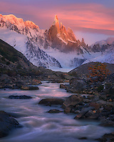 Glaciated waters under the alpenglow of sunrise light on Cerro Torre, puncuated by fall color.