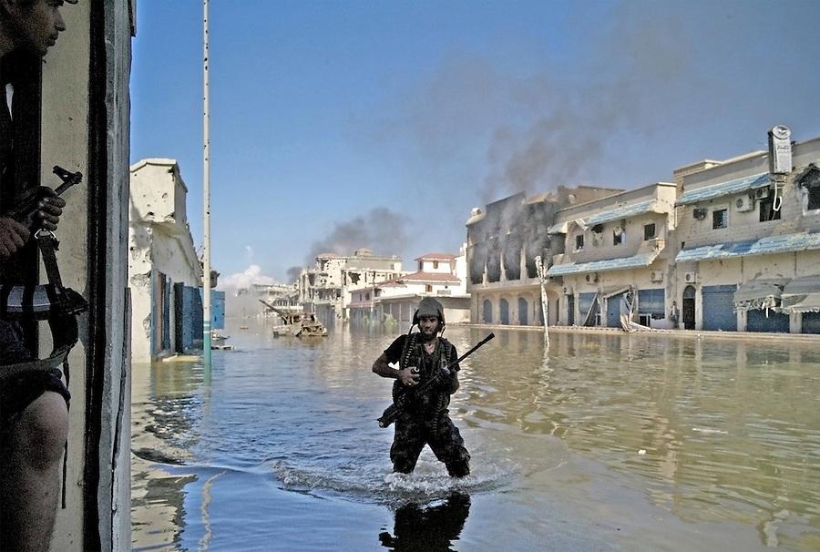 An anti-Gaddafi fighter wades through flooded battle-torn street in Sirte, Libya.