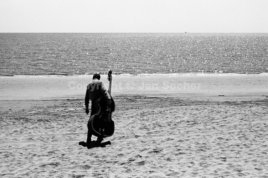 A Mexican musician from a Mariachi band carries his contrabass on the beach in Los Mochis, Mexico, 21 September 1998.