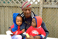 African American dad holding sons age 30 and 2. In the Heart of the Beast May Day Festival and Parade Minneapolis Minnesota USA