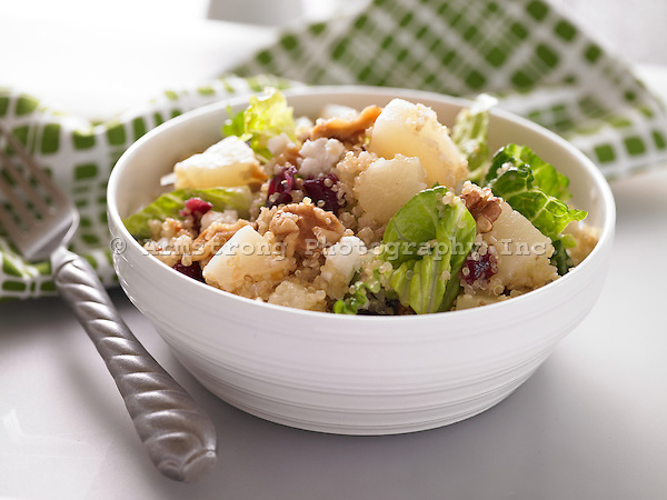 Quinoa salad in a bowl with lettuce, walnuts, pears, and dried cranberries.