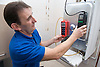 Gas man testing a boiler using special equipment,