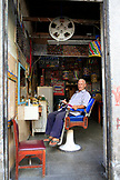 BRAZIL, Rio de Janiero, Lapa, Lavradio Street, Barber Mario Carnivale sits inside of his shop