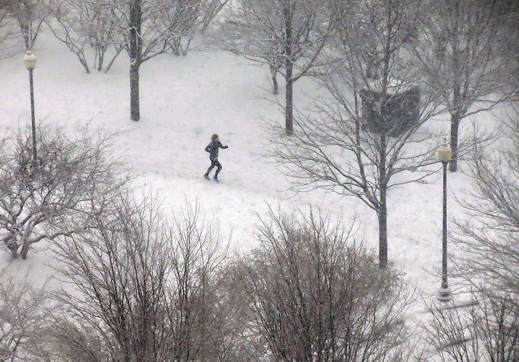 Chicago scenes:  A runner makes her way through the falling snow along the Lake Shore Drive trail near the Streeterville neighborhood in Chicago. (Photo by Jamie Moncrief)