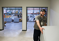 NWA Democrat-Gazette/CHARLIE KAIJO Plumber Matt Woods pushes a cabinet he will install, Thursday, January 10, 2019 at the new Bentonville School District Warehouse in Bentonville. <br /><br />The new warehouse will house food commodities, district supplies, paper supplies, adventure club and child enrichment services supplies and snack packs for the students.