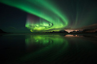 Northern Lights reflect on beach in winter, Moskenesøy, Lofoten Islands, Norway