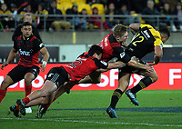 David Havili and Jack Goodhue try to stop Ngani Luamape during the Super Rugby match between the Hurricanes and Crusaders at Westpac Stadium in Wellington, New Zealand on Saturday, 15 July 2017. Photo: Dave Lintott / lintottphoto.co.nz