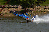 """Frame 2: Greg Hopp in the U-100 """"Leland Unlimited"""" gets airborne entering turn 1 during qualifying, does a """"blowover"""", lands rights side up down but backwards, digs in and flips upside down. The safety crew rescues Hopp through the trapdoor in the bottom. The boat suffered damage to the left sponson, Hopp had no injuries but was done for the weekend."""