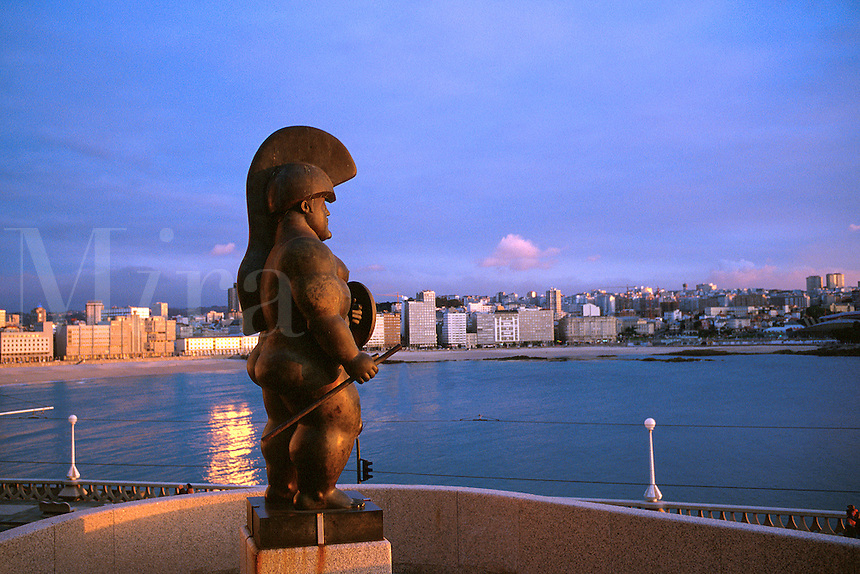 Spain, Galicia, La Coruna. Statue of Hercules, office buildings and hotels along Orz n beach in background. La Coruna Galicia Spain.