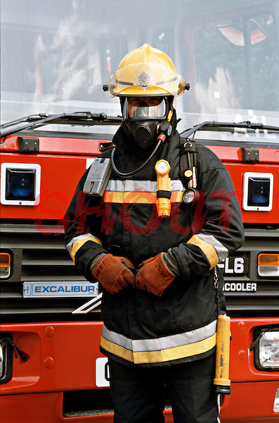 Firefighter in full fire kit wearing breathing apparatus stood in front of a fire engine. This image may only be used to portray the subject in a positive manner..©shoutpictures.com..john@shoutpictures.com