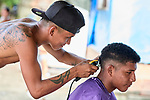 A young man gives a haircut to another in the Nacoes Indigenas neighborhood in Manaus, Brazil. The neighborhood is home to members of more than a dozen indigenous groups, many of whose members have migrated to the city in recent years from their homes in the Amazon forest.
