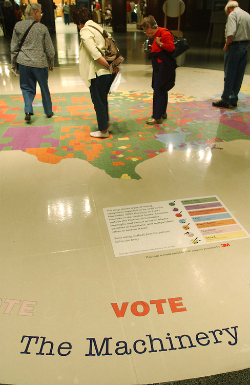 "10/05/04.MACHINERY OF DEMOCRACY--Visitors examine a United States map that shows types of voting equipment expected to be used across the nation in November's elections. The map is color-coded to indicate the type of device expected to be used in each of the nation's 3,141 counties. It is part of the ""Vote"" exhibit at the National Museum of American History..CONGRESSIONAL QUARTERLY PHOTO BY SCOTT J. FERRELL"