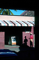 Shadow of man with pork pie hat checking his wallet, Bridgetown Barbados, Caribbean,1975