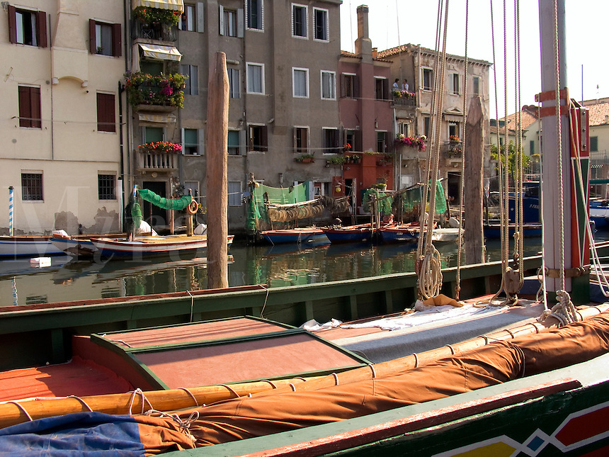 Fishing boats and houses along canal in Chioggia Ital