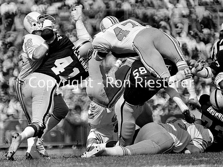 Oakland Raiders Phil Villapiano, and Monte Johnson upend Houston Oilers...Rob Carpenter, amd Ronnie Coleman...(1977 photo/Ron Riesterer)