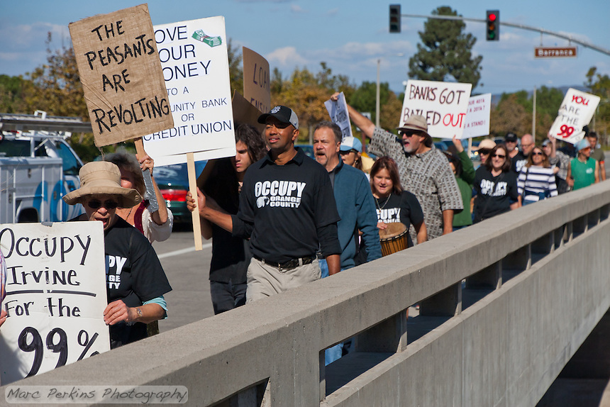 The Occupy Orange County, Irvine march on Saturday November 5 crosses a bridge near the intersection of Barranca and Harvard in Irvine, CA.  Many protesters can be seen holding signs with cars in the background.