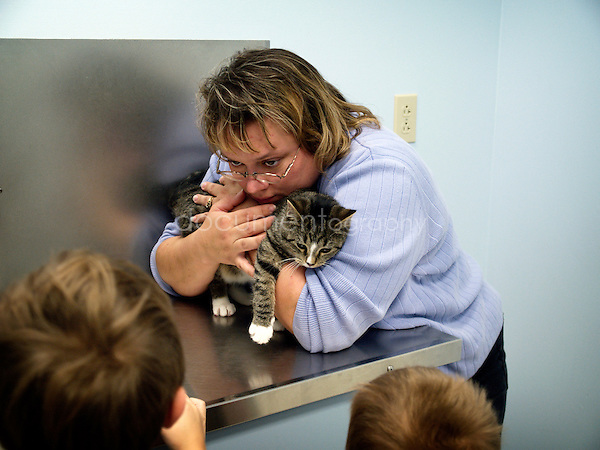 A woman bringing with her children her cat to the vet.