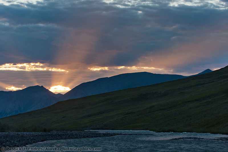 Midnight sun sets over the Marsh Fork of the Canning River, Brooks Range mountains, Arctic National Wildlife Refuge, Arctic, Alaska.