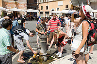 People refresh themself in a fountain in downtown during a very hot day..Turisti si rinfrescano in una fontana nel centro di Roma