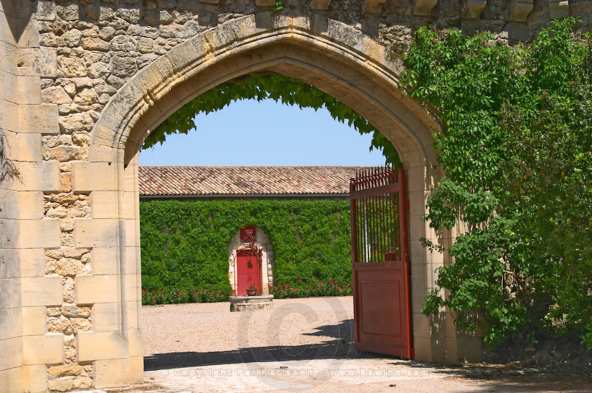 One of the side gates with an arched portico leading in to the main court yard and a water well Chateau de Pressac St Etienne de Lisse Saint Emilion Bordeaux Gironde Aquitaine France