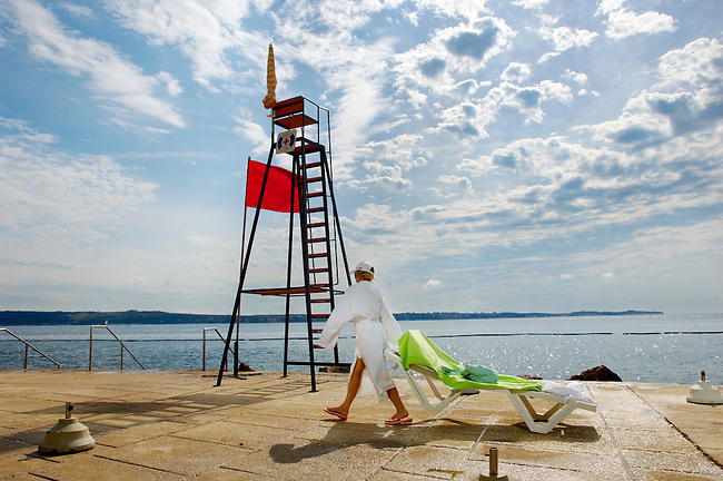Sunbathers preparing a sun bed on a sea terrace. Piran , Slovenia