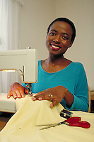 Afro-American female using sewing machine, with cloth, scissors, and pins, in home setting. California.