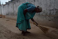 A local villager sweeps the floor as part of the daily chores of cleaning the surroundings of their houses in Mecharajupalli village in Telangana, India.
