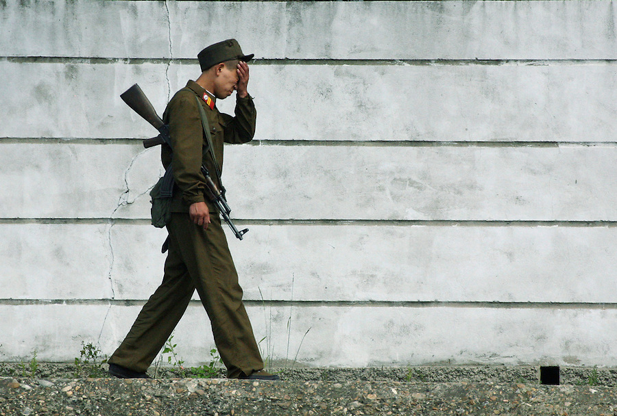"""A North Korean soldier walks along the river port town of Sinuiji July 8, 2006. China and North Korea are separated by the Yalu River, upon which Chinese tourists take pleaure cruises across the water to  observe their less economically developed neighbors.  North Korea has threatened to take """"stronger physical actions"""" after Japan imposed punitive measures in response to its barrage of missile tests and pushed for international sanctions. North Korea has vowed to carry out more launches and has said it will use force if the international community tries to stop it. DPRK, north korea, china, dandong, border, liaoning, democratic, people's, rebiblic, of, korea, nuclear, test, rice, japan, arms, race, weapons, stalinist, communist, kin jong il"""