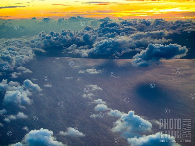 Early morning clouds cover the Big Island's Hawi during sunrise, as seen from an airplane.