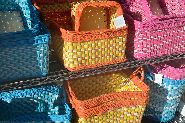 Coloured woven baskets in a shop window display.