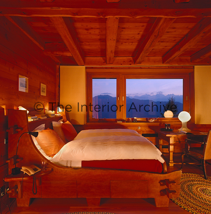 A rustic sleigh bed in a chalet with a view of the mountains