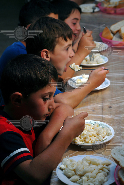 Children eat dinner together at a refugee camp for IDP's (Internally Displaced Persons) fleeing violence in the South Ossetia region. This camp, which currently houses 160 IDPs, is normally used as a Patriotic Summer Camp for Youth in Tokhliauri...