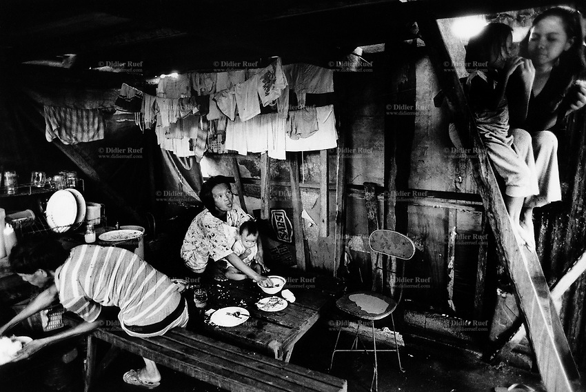 Philippines. Luzon Region. Manila. Tondo area. Smokey mountain is a rubbish dump. Life on a garbage heap. The Ragaza family eats lunch. Father, mother, three children. Brothers and sisters. Clean laundry dries on linen. © 1992 Didier Ruef ..