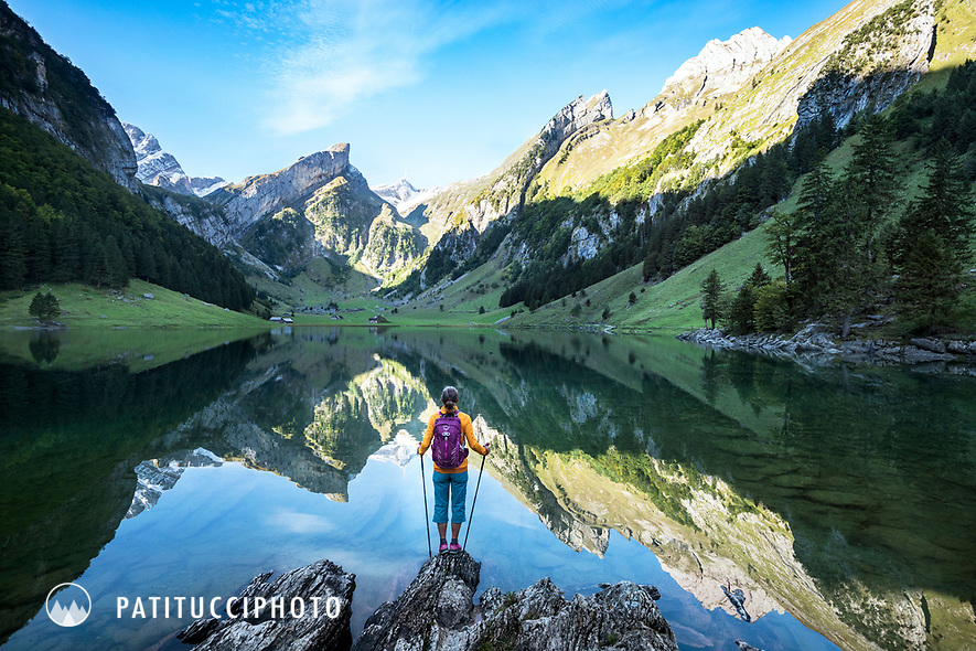 A woman hiker stands on the shore of the Seealpsee, looking at the reflection of the Santis and Alpstein mountains. Switzerland.