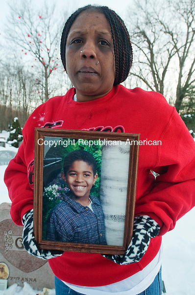WATERBURY, CT 020714JS15- FEBRUARY 11, 2014_ Tamara Dawkins of Naugatuck, holds a picture of her son, Torrance Dawkins,  when he was 6 years old on Tuesday at his gravesite. Tamara along with family and friends, held a graveside vigil at All Saints Cemetery in Waterbury for Torrance, who was killed outside a nightclub in New Haven in August. Tamara is frustrated because no arrests have been made six months after the shooting. Jim Shannon Republican-American