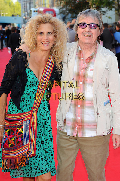 Molly Wyman & Bill Wyman .Arrivals to the UK Premiere of 'George Harrison: Living In The Material World' at BFI Southbank, London, England..October 2nd, 2011.half length black white jacket check shirt sunglasses shades married husband wife green print dress bag purse red .CAP/CJ.©Chris Joseph/Capital Pictures.