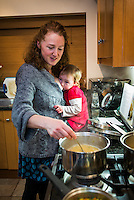A woman stirs as saucepan of soup and breastfeeds her 20 month old toddler at the same time.  The toddler is sitting on the kitchen work top.<br /> <br /> 07/02/2013<br /> Hampshire, England, UK