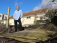 BNPS.co.uk (01202 558833)<br /> Pic: CorinMesser/BNPS<br /> <br /> Dave Thorne with smashed garden fence.<br /> <br /> Homeowners are counting the cost today after a 'tornado' hit a south coast town overnight.<br /> <br /> Residents in Barton-on-Sea, Hants, were woken at 4am as the twister blasted its way through the town like an 'express train'. <br /> <br /> The strength of the winds of up to 80mph shook numerous houses, sending roof tiles smashing to the ground.<br />  <br /> A 30ft long brick wall collapsed under the strength of the gusts while fence panels were flung through the air.<br /> <br /> Part of a garden shed that had been picked up by the tornado smashed a hole through the windscreen of a car.