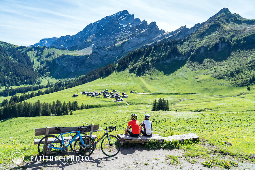 Cyclists relaxing in the sun while gravel road riding near the Col de la Croix, above Villars, Switzerland.