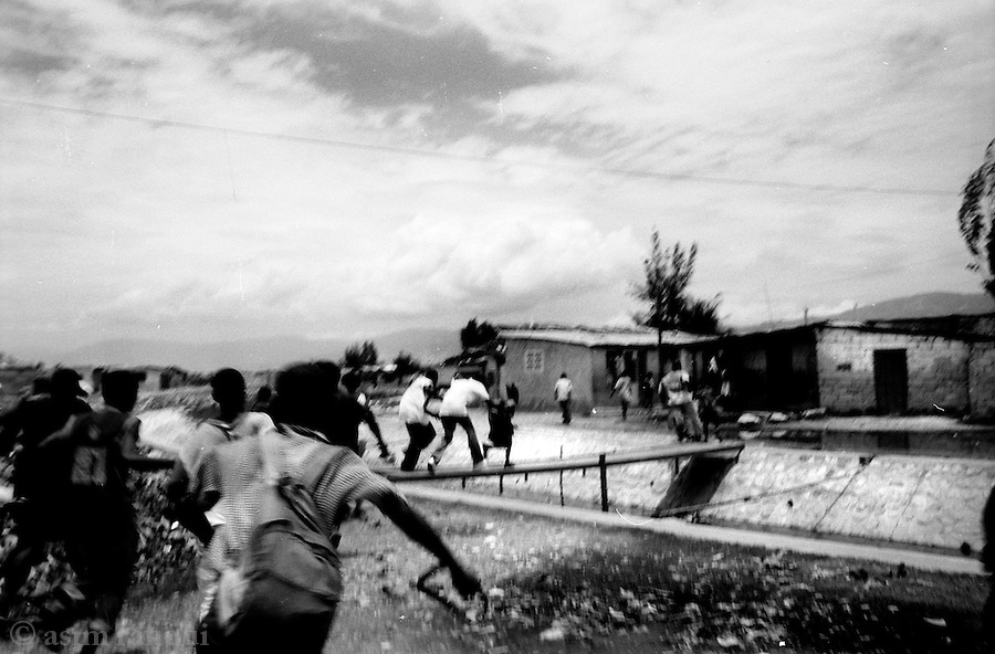 people scramble to escape gun fire directed at a pro-aristide march as it made its way into cite soleil - the source of the gun fire was unclear, but the haitian national police was suspected as they have frequently fired at unarmed pro-aristide demonstrators in the past resulting in many deaths and injuries<br />