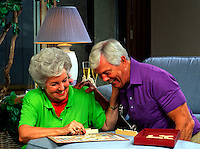 A smiling senior couple has fun while playing a game.