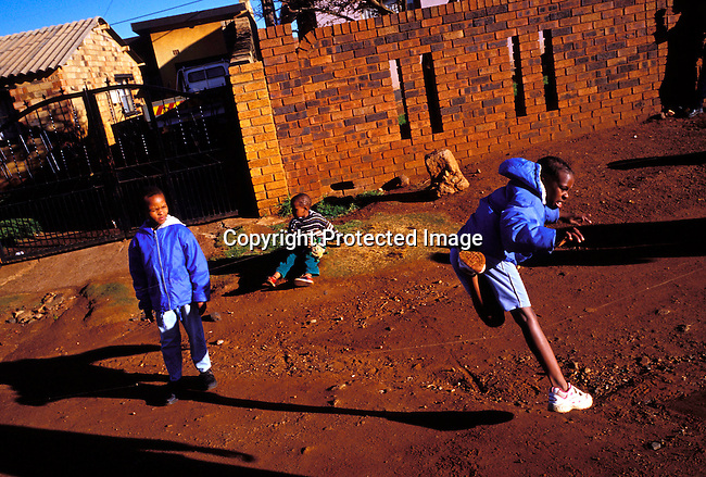dippchi00234 Children SOWETO, SOUTH AFRICA - JULY 15: Unidentified girls playing in the street outside their home on July 15, 2002 in Soweto, a black township outside Johannesburg, South Africa. Soweto is the largest township in the country and itÕs estimated that about 3-4 million people resides there..©Per-Anders Pettersson/ iAfrika Photos..