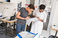 """Das Berliner Start-up """"mimycri"""" produziert Taschen aus den Gummiplanen gestrandeter Fluechtlingsboote.<br /> Statt Griechenlands Straende im Muell der gestrandeten Fluechtlingsboote ersticken zu lassen, stellt das Berliner Unternehmen """"mimycri"""" daraus Taschen und Rucksaecke her und bietet Fluechtlingen eine Chance auf Normalitaet und Regelmaessigkeit.<br /> Im Bild vlnr.: Nora Azzaoui, 30-Jaehrige Unternehmensberaterin aus Berlin und Abid Ali, gefluechteter Schneider aus Pakistan besprechen den Schnitt fuer eine Tasche.<br /> 8.8.2017, Berlin<br /> Copyright: Christian-Ditsch.de<br /> [Inhaltsveraendernde Manipulation des Fotos nur nach ausdruecklicher Genehmigung des Fotografen. Vereinbarungen ueber Abtretung von Persoenlichkeitsrechten/Model Release der abgebildeten Person/Personen liegen nicht vor. NO MODEL RELEASE! Nur fuer Redaktionelle Zwecke. Don't publish without copyright Christian-Ditsch.de, Veroeffentlichung nur mit Fotografennennung, sowie gegen Honorar, MwSt. und Beleg. Konto: I N G - D i B a, IBAN DE58500105175400192269, BIC INGDDEFFXXX, Kontakt: post@christian-ditsch.de<br /> Bei der Bearbeitung der Dateiinformationen darf die Urheberkennzeichnung in den EXIF- und  IPTC-Daten nicht entfernt werden, diese sind in digitalen Medien nach §95c UrhG rechtlich geschuetzt. Der Urhebervermerk wird gemaess §13 UrhG verlangt.]"""