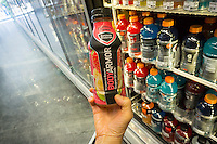 A shopper chooses a bottle of BodyArmor sports drink in a convenience store in New York on Thursday, August 13, 2015. Dr Pepper Snapple Group has bought an 11.7% interest  for $20 million in BodyArmor, a competitor to Gatorade. NBA player Kobe Bryant is also an investor. The drink is considered healthier than its rivals Gatorade and Powerade as it uses cane sugar, not high-fructose corn syrup as a sweetener.  (© Richard B. Levine)